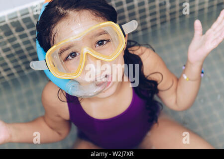 portrait of a funny pretty little girl with snorkel goggles in the tub while taking a bath in the bathtub, kids hygiene concept - Stock Image