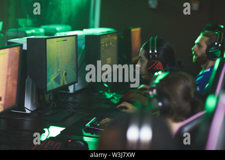 Young addicted men in headsets for online communication sitting in row and participating in cyber game - Stock Image
