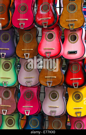 Several guitars of different colors hanging in rows on a wall. - Stock Image