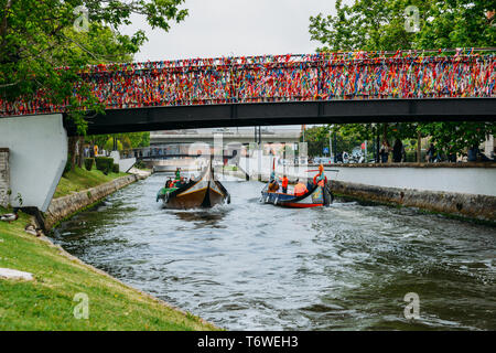 Aveiro, Portugal - April 29, 2019: Traditional boat, Moliceiro, transporting tourists passing under bridge covered in confetti on canal at Aveiro - Stock Image