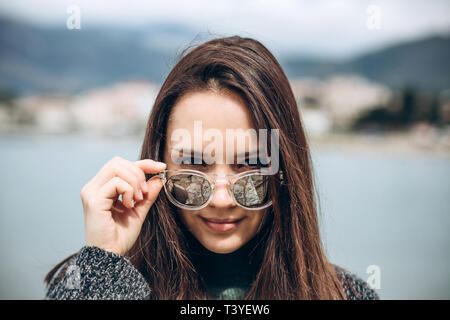 Portrait of a beautiful young fashionable girl on the background of the sea and the coastal city. - Stock Image