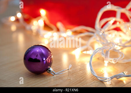 Purple round glass christmas ball on the floor with white holiday lights - Stock Image
