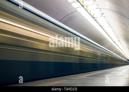 Train in motion blur arriving at subway station. - Stock Image