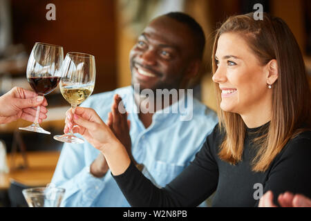 Young woman toasting with wine as birthday congratulation in bistro - Stock Image