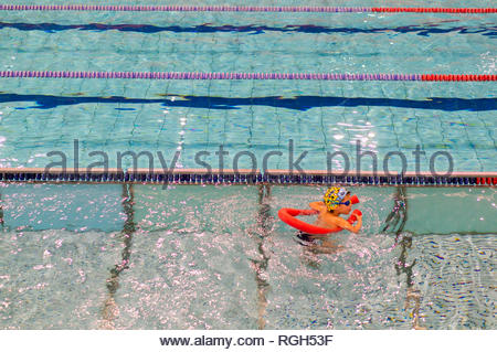Poznan, Poland - January 26, 2019: Young boy learning to swim with a stick during swimming leasson in the Termy Maltanskie. - Stock Image