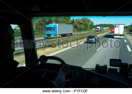 Truck driver heading north on the A3 autobahn in Germany. - Stock Image