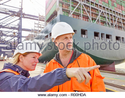 Portrait of docks worker and manager talking infront of cargo ship and cranes - Stock Image