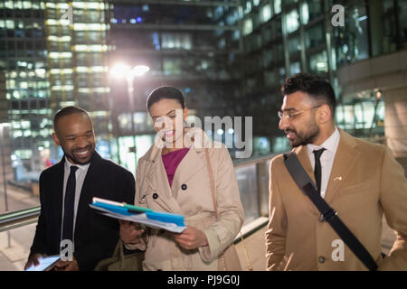 Business people walking and discussion paperwork in city at night - Stock Image