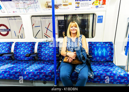 Woman on her own using London underground, Woman on her own using London tube train, Sat on London tube train, sitting down on tube train, UK, England - Stock Image