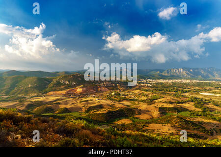 Panorama of the San Giorgio basin, with the town of Iglesias in the background and the ancient mines of Monteponi. Sky after a storm. Italy, Sardinia  - Stock Image