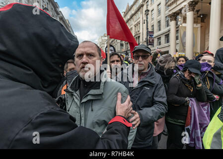 London, UK. 9th Dec, 2018. A couple of men who had walked into the march are asked to leave. The united counter demonstration by anti-fascists was marching in opposition to Tommy Robinson's fascist pro-Brexit march. The march which included both remain and leave supporting anti-fascists gathered at the BBC to to to a rally at Downing St. Police had issued conditions on both events designed to keep the two groups well apart. Credit: Peter Marshall/Alamy Live News - Stock Image