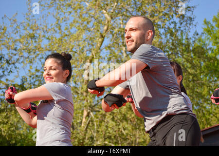 Nis, Serbia - April 20, 2019 Group of young attractive people practicing Piloxing sport in an outdoor class in summer with instructor - Stock Image
