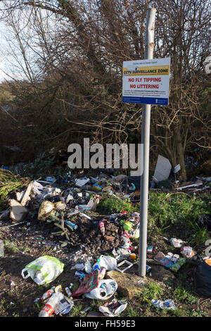 Fly tipping rubbish dumped in the countryside alongside a warning notice - Stock Image