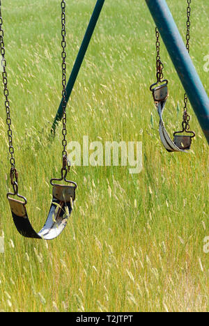 Rusted and abandoned playground swings with strap seats on the Canadian Prairies, Alberta - Stock Image