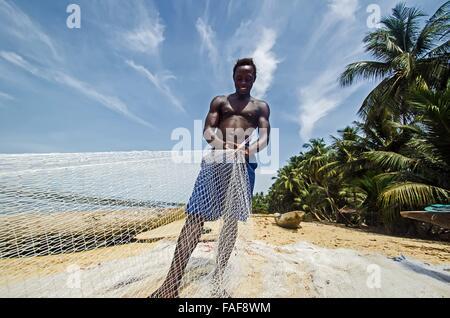 Fisherman fixing his nets on the beach on Yele Island, the Turtle Islands, Sierra Leone. - Stock Image