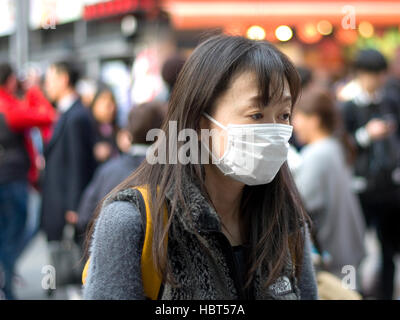 Japanese women wearing a surgical face mask. - Stock Image