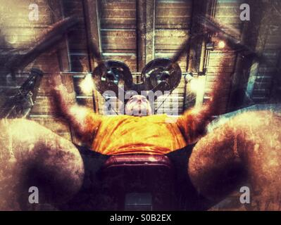 Middle aged caucasian man working out on a pectoral fly / butterfly machine in a fitness studio. - Stock Image
