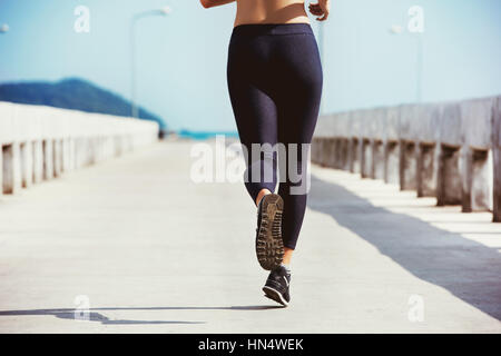 Closeup photo of running girl on sea pier. Space for text - Stock Image