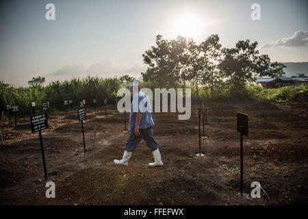 An Ebola worker walks through a graveyard of Ebola victims in Kenam, Sierra Leone - Stock Image