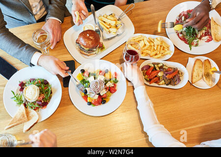 Friends over a hearty lunch or dinner together in the restaurant - Stock Image