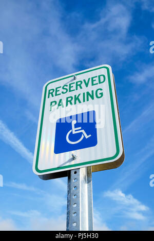 Handicap parking sign or disabled parking sign from low angle, isolated against blue sky. - Stock Image