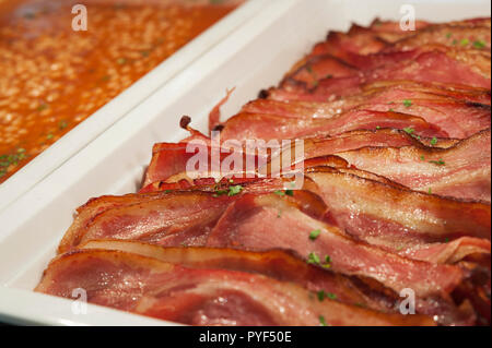 Closeup shot of trays of sliced grilled bacon and baked beans, healthy cooked breakfast options, adding protein and fiber to a diet - Stock Image