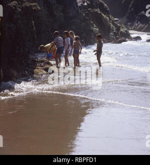 1960s, a small group of children looking for crabs in shallow sea water by the rocky cliffs on the beach at Llangrannog, Wales. This beautiful, secluded bay is a icon of Welsh culture and over the years has provided wonderful childhood memories for many and has remained remarkably unchanged. - Stock Image