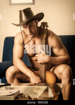 Muscular young man with guitar and cowboy hat - Stock Image