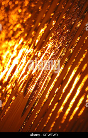 An abstract background of orange sunlight reflecting on seashore sands. - Stock Image