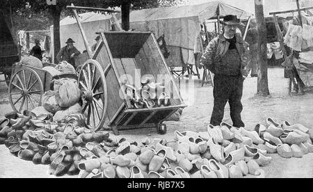 Display of wooden shoes (sabots) for sale in a Breton market, Brittany, Northern France. Each shoe is carved from a single piece of wood. - Stock Image