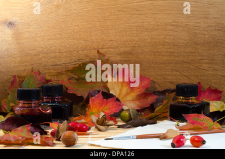 A still life arrangement of autumn leaves and windfall, bottles of coloured inks and paintbrush with space for text - Stock Image