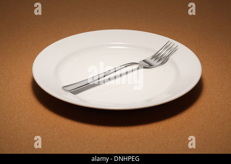 A dinning fork on a empty white dinning plate. - Stock Image