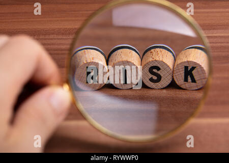 Close-up Of Human Hand Inspecting Risk Word On Cork Over Wooden Desk - Stock Image