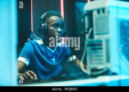 Serious young Afro-American gamer in football tshirt wearing headset with microphone sitting at table and playing network game - Stock Image