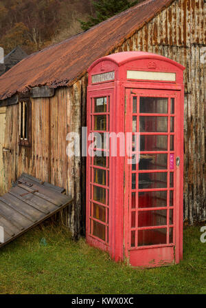 An old iconic red telephone box stands next to rusting huts in the village of Diabaig in the Torridon area of the - Stock Image