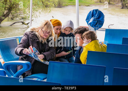 Nature Reserve Delta of the Danube River. Romania. April 20, 2019. A cruise ship swims along the river. Tourists on the deck look at the route map. - Stock Image