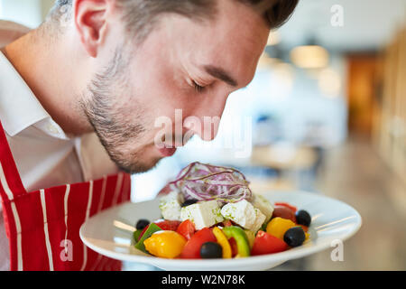 Waiter serving fresh and tasty greek salad in the restaurant - Stock Image