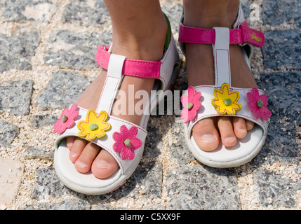 Close up of a pair of sandals decorated with pink and yellow flowers worn by a young girl - Stock Image