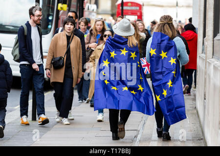 London, UK. 23 March 2019. Tow women with EU flags. Remain supporters and protesters take part in a march to stop Brexit in Central London calling for a People's Vote. - Stock Image