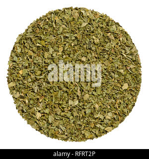Dried lovage. Herb circle from above, isolated, over white. Disc made of grated lovage leaves, Levisticum officinale. Edible green herb and vegetable. - Stock Image