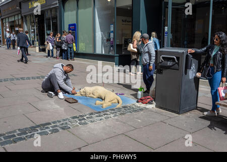 Street artist making a sand sculpture of a dog in the city of Bath with passers by in the background - Stock Image