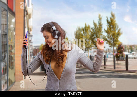 Young woman listening to music moving her body - Stock Image