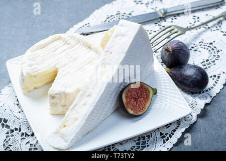 Two pieces of French soft cheeses Brie and Camembert with white mold and strong odor, served with fresh ripe figs close up - Stock Image