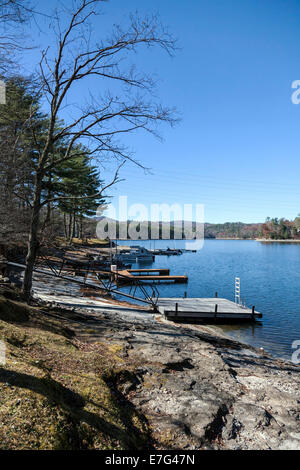 Wooden floating docks and boats along the rocky shore of Lake Glenville near Cashiers, North Carolina on an autumn - Stock Image