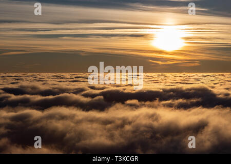 Beautiful sunset over a valley filled by fog with mountains and hills. - Stock Image