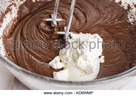Sweet sour cream in the chocolate cream with hand mixer. - Stock Image