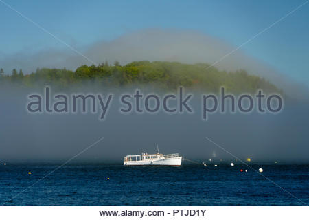 White boat anchored in Frenchman Bay as morning mist is rising from the water,  Bar Harbor, Maine, USA. - Stock Image