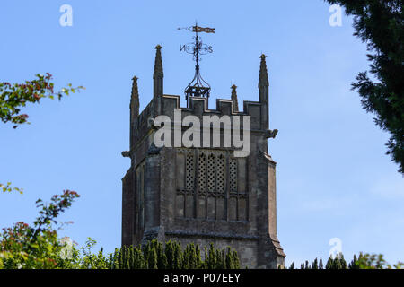 Square flat roof church tower with fancy weather vane above trees against a blue sky - Stock Image