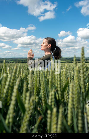 woman standing in a field of wheat meditating, yoga pose. - Stock Image
