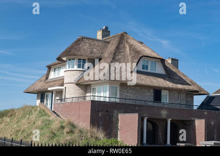 Netherlands, zeeburg, 2017, An stunning example of a thatched roof on a red bricked house looking out over the north sea.  While once a sign of povert - Stock Image